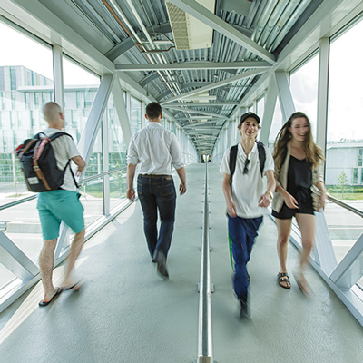 Photo of students using the enclosed Woodroffe avenue overpass connecting the ACCE building to the rest of the campus.